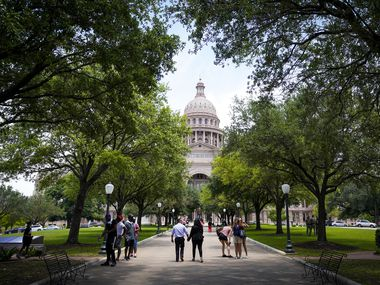 People walk on the grounds of the Texas Capitol during the 87th Texas legislature on Friday, May 7, 2021, in Austin. (Smiley N. Pool/The Dallas Morning News)