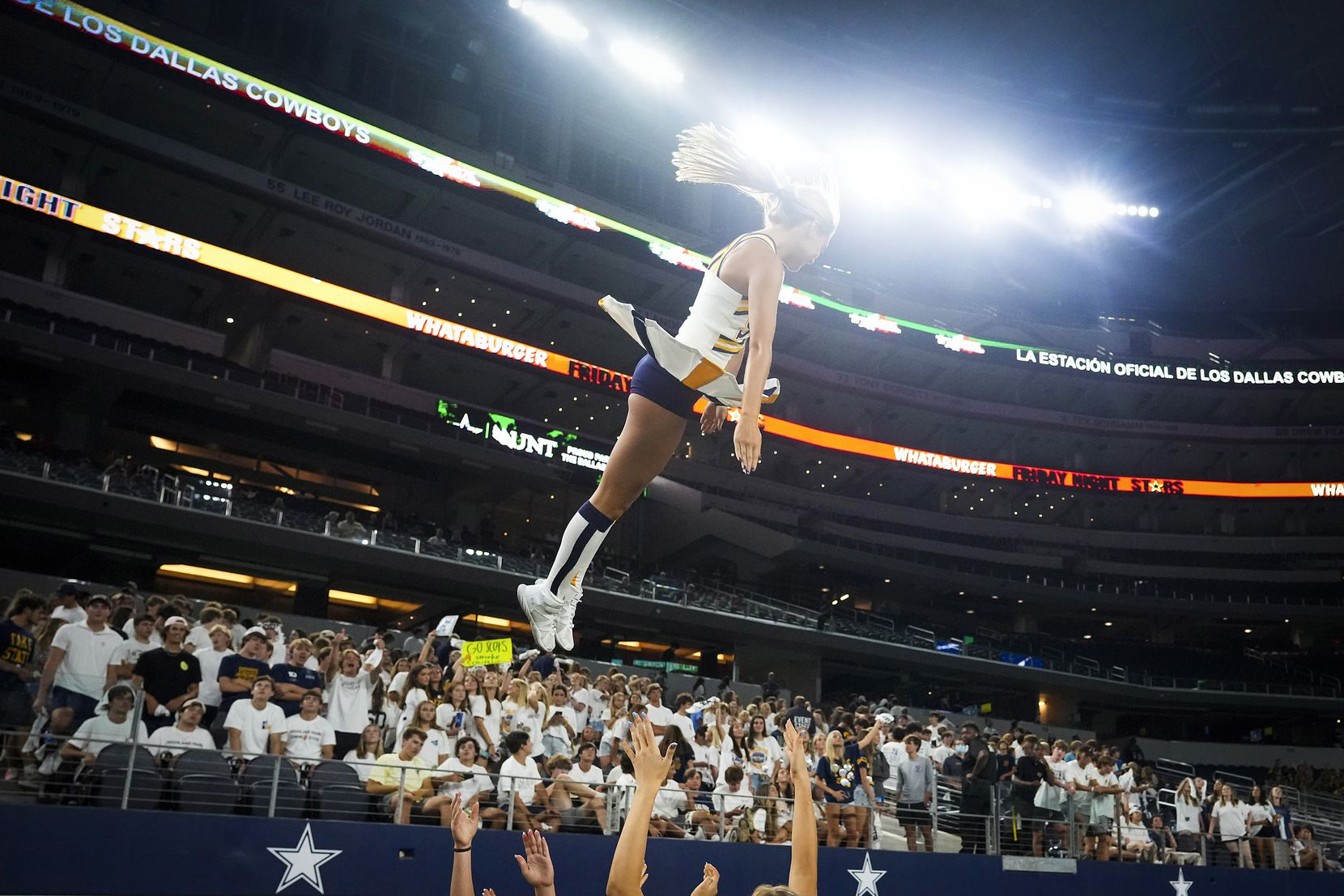 A Highland Park cheerleader is tossed into the air during the second half of a high school football game Southlake Carroll at AT&T Stadium on Thursday, Aug. 26, 2021, in Arlington.