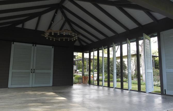 The new carport was designed as a multifunction space. A small storage space behind the blue doors hides a work bench and garden tools. The owners also stage parties here.