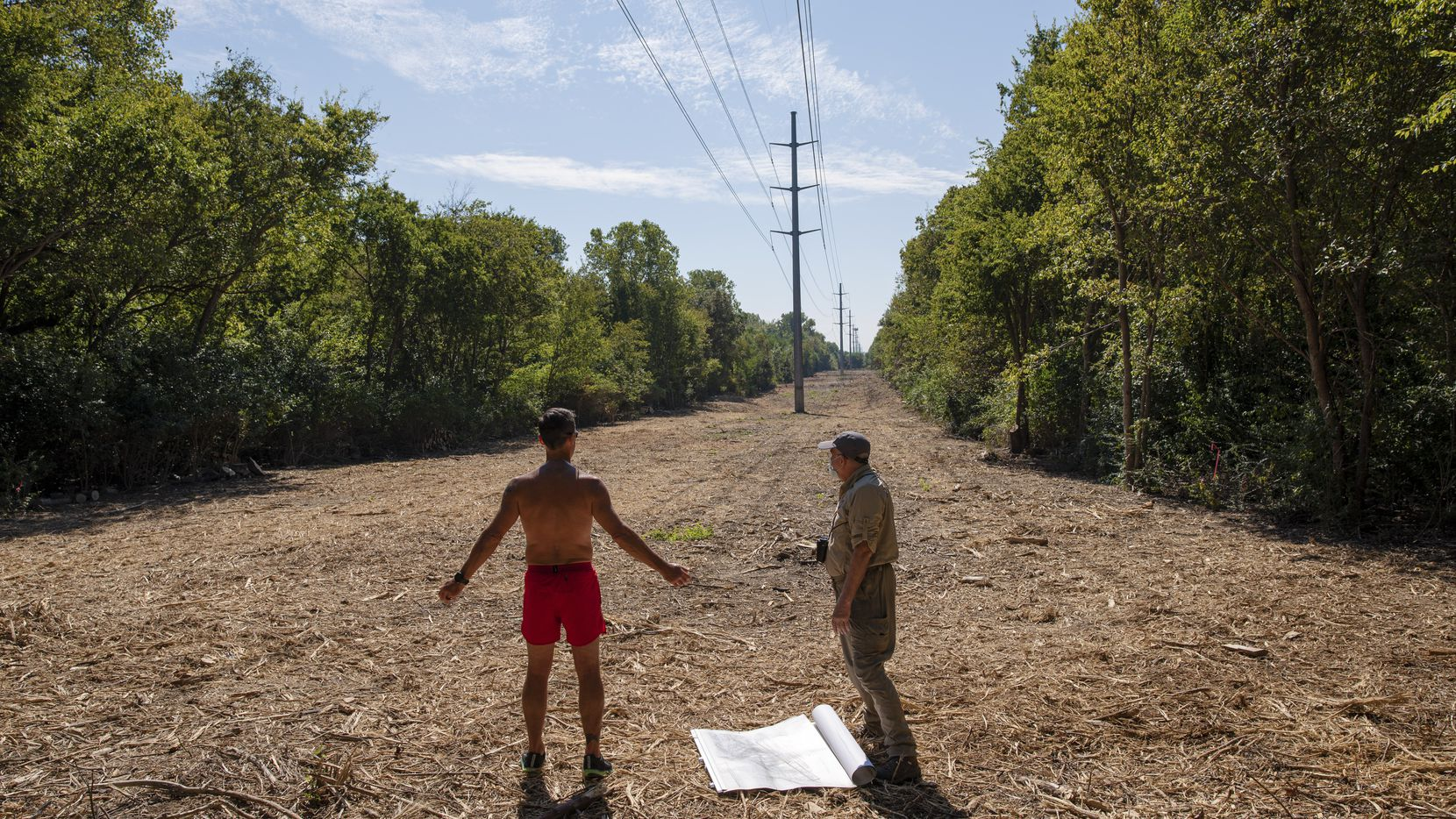 White Rock resident and runner Eric Griffin, left, and environmental activist Kelly Cotten, right, speak about the area of the Old Fish Hatchery Nature Area after an Oncor contractor cleared out land, Thursday in Dallas. Griffin, who knew about the clear out of land, was on a daily run and started speaking to Cotten about the incident.