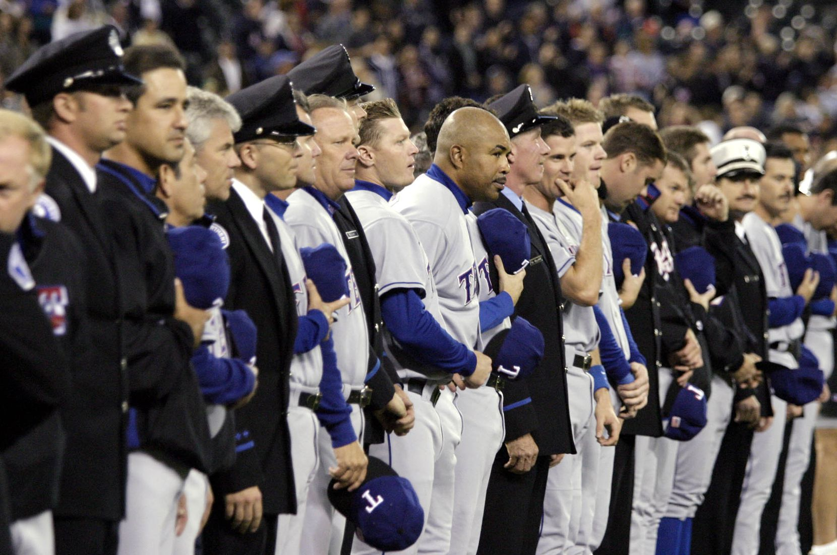 Members of the Texas Rangers stand interspersed with firefighters, EMTs and police from the Seattle area during a ceremony to remember those who died in the terrorist attacks of Sept. 11, 2001, before the game between the Seattle Mariners and the Texas Rangers in Seattle, Thursday, Sept. 11, 2003.