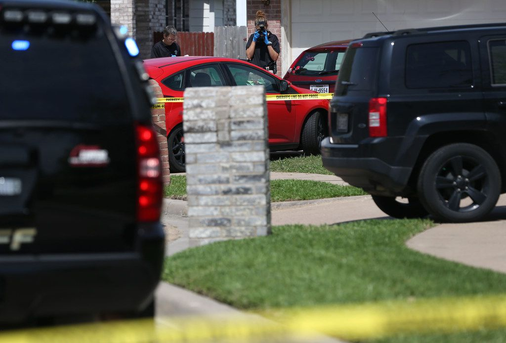 A crime scene photographer takes a photo of a vehicle in the driveway of the Ponder home where Wednesday's shooting occurred. (Rose Baca/Staff Photographer)