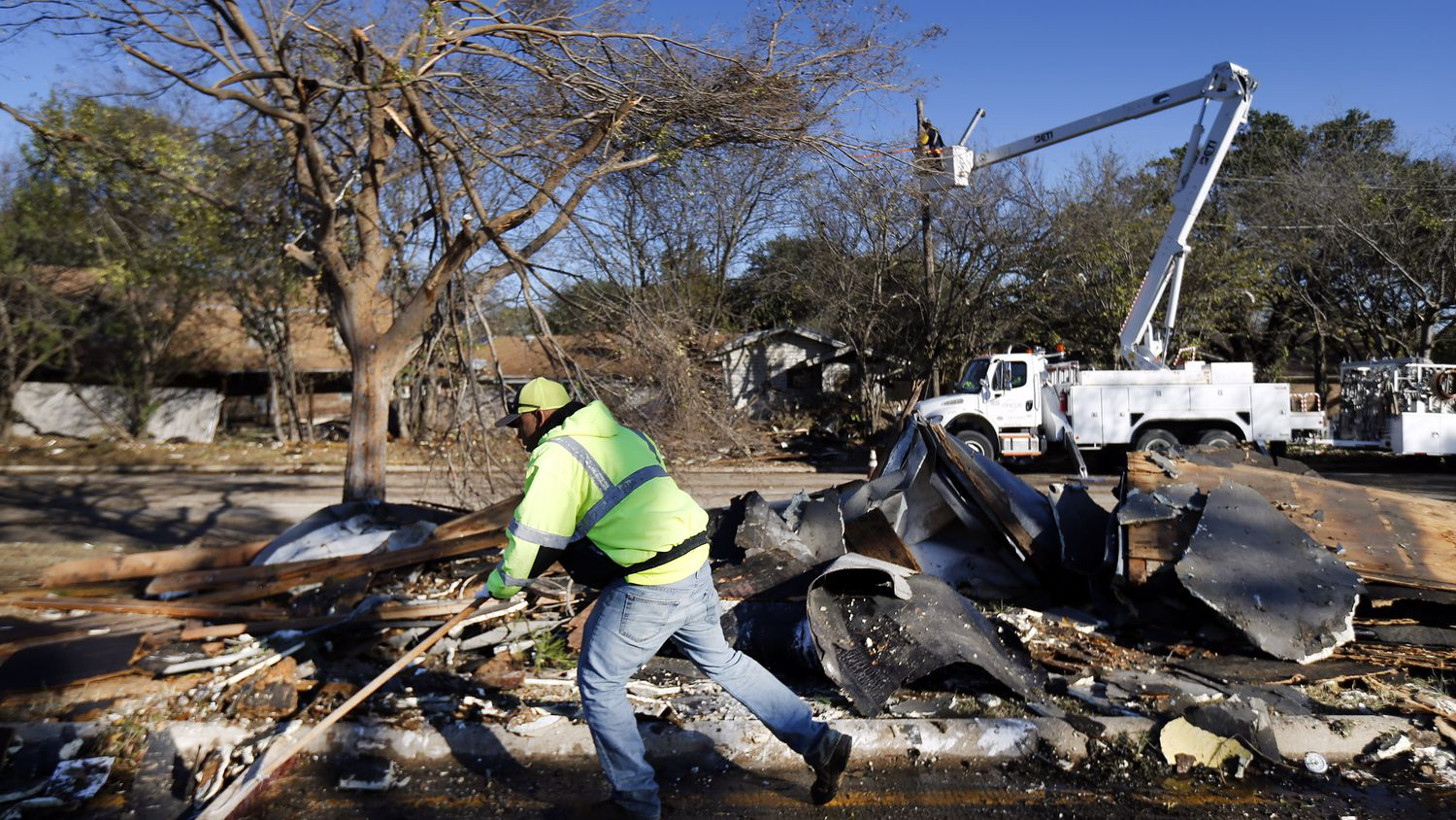 A City of Arlington street crewman cleans up debris from The Mirage Apartments complex along Pioneer Parkway in Arlington, Wednesday, November 24, 2020, after a tornado-warned storm torn the roofing off. Air conditioner units and other structural debris were scattered across the property and street. The crew is trying to get the major thoroughfare open.