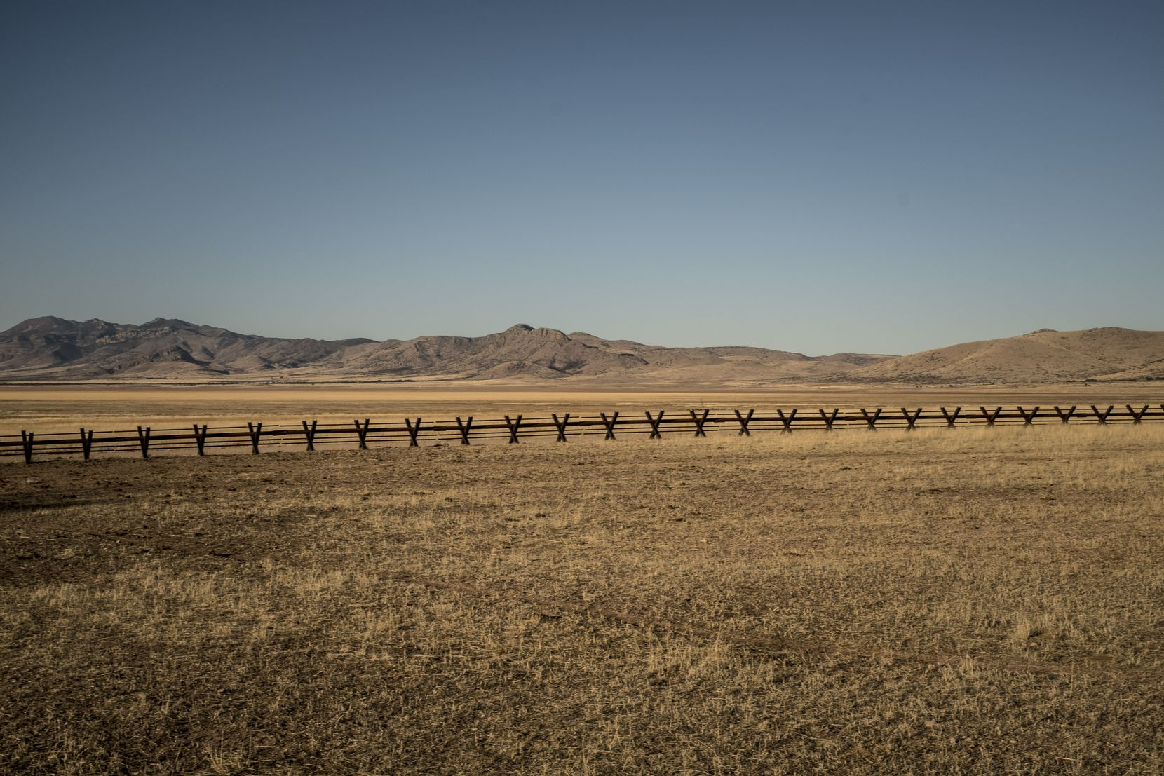The border fence, here composed of X-shaped barriers, passes through ranching land on the border between the state of New Mexico and the country of Mexico, west of El Paso, TX on Jan. 31, 2017. Here, rows of wheat and alfalfa fill the farmland along the edge of Mexico. If a new wall comes, farmers wonder what will happen to Americans who rely on migrant labor. (Bryan Denton/The New York Times)
