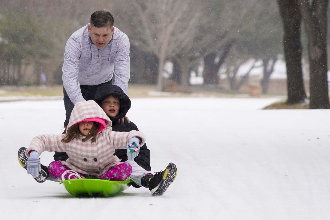 Mae, 9, and Vaughn, 11, Scrogginthorpe get a push from their dad Micah Scrogginthorpe they sled in the empty street front of the home in Richardson as a winter storm brings snow and freezing temperatures to North Texas on Sunday, Feb. 14, 2021.  A winter storm watch has been issued for all of North Texas, including Dallas, Denton, Collin and Tarrant counties and will be in effect from late Saturday through Monday afternoon.