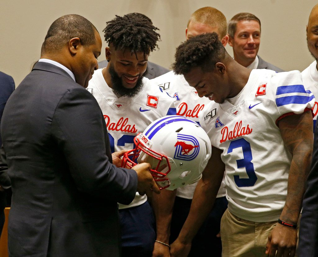 Dallas Mayor Eric Johnson takes a look at the newly designed SMU football helmet with Southern Methodist Mustangs safety Rodney Clemons (23), Southern Methodist Mustangs quarterback Shane Buechele (7) and Southern Methodist Mustangs wide receiver James Proche (3) at Dallas City Hall in Dallas on Wednesday, September 25, 2019. SMU defeated TCU 41-38 last week to win back the Iron Skillet for the first time since 2011. (Vernon Bryant/The Dallas Morning News)