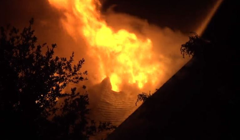 Fire burns through the roof of a home in Keller on Wednesday morning. Lightning was suspected as the cause.