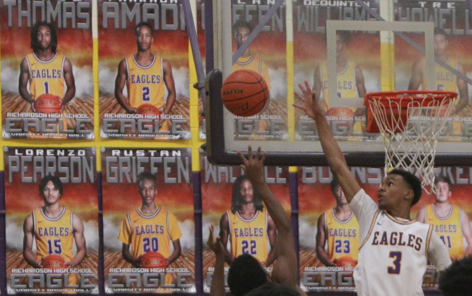 Richardson's Rylan Griffen (3) skies to block the shot of Lake Highland guard Jalen Majors (2) during first half action. A poster with Griffen's likeness is in the background just behind the basketball. The two teams played their District 7-6A boys basketball game at Richardson High School in Richardson on January 15, 2021.