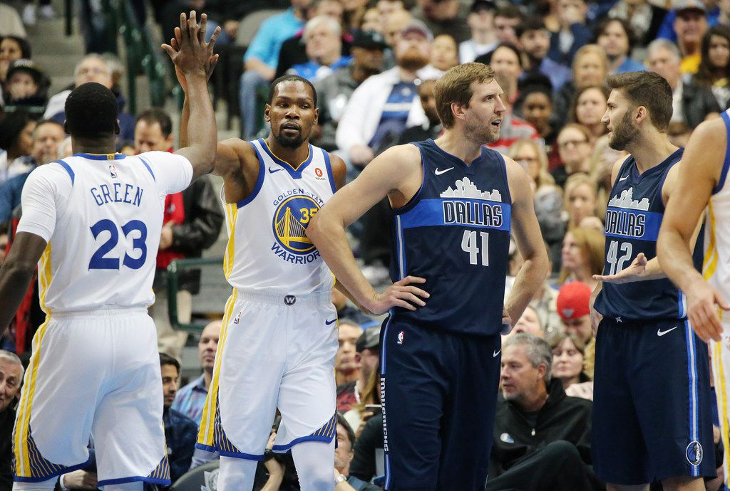 Golden State Warriors forward Kevin Durant (35) congratulates forward Draymond Green (23) after a play as Dallas Mavericks forward Dirk Nowitzki (41) and forward Maximilian Kleber (42) stand nearby in the first half during a National Basketball League game at the American Airlines Center in Dallas Wednesday January 3, 2018. Warriors led the Mavericks 67-61 at the half. (Andy Jacobsohn/The Dallas Morning News)