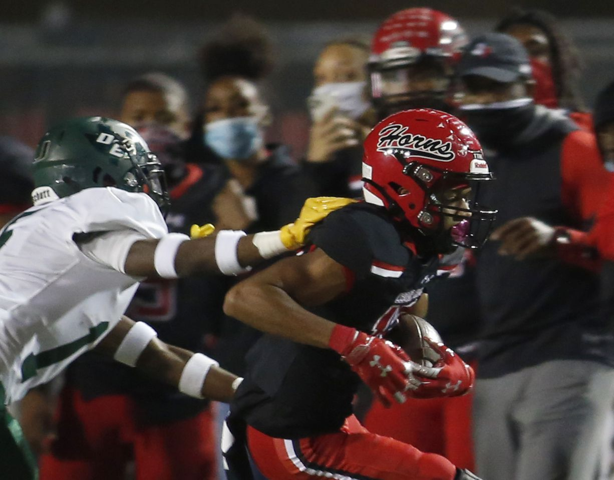 Cedar Hill Longhorns receiver Javien Clemmer (13) tacks on yardage after a reception as DeSoto defensive back Ashton Levells-Mitchell (15) moves in to force him out of bounds during second quarter action. The two teams played their District 11-6A  football game at Longhorn Stadium in Cedar Hill on November 6, 2020. (Steve Hamm/ Special Contributor)