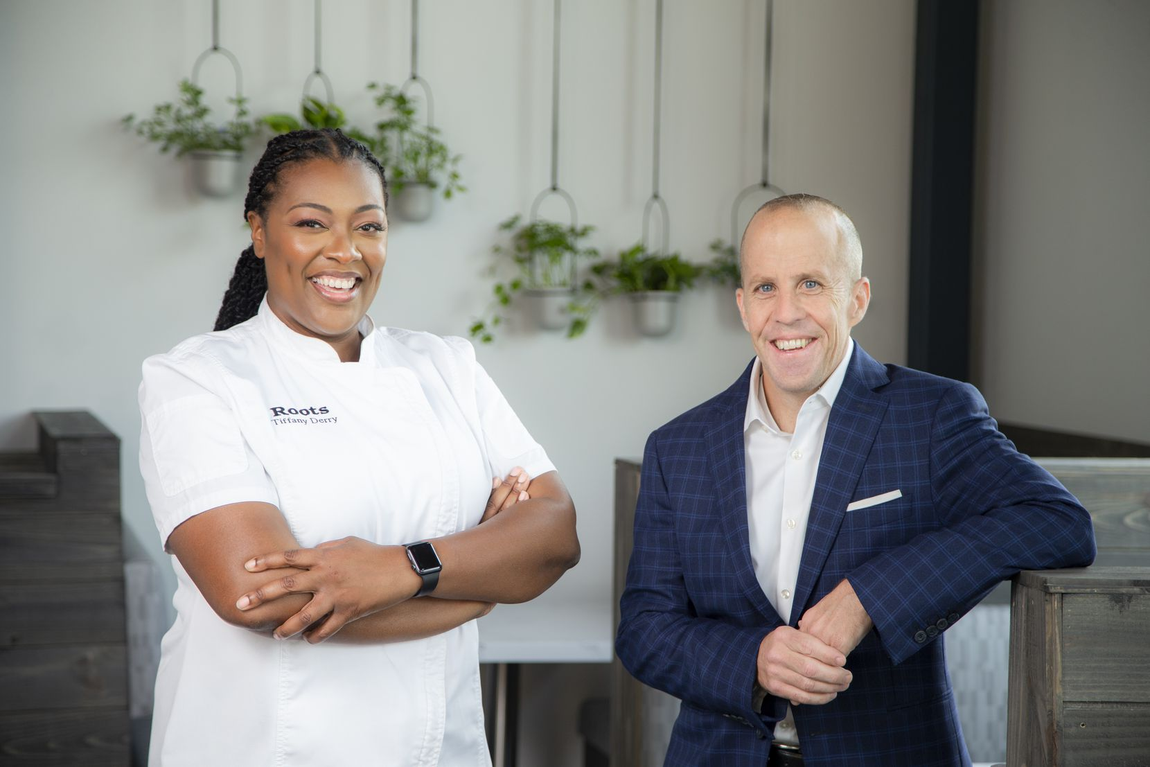 Chef-Owner Tiffany Derry, left, and owner Tom Foley pose for a photo at their restaurant, Roots Southern Kitchen, in Farmers Branch.