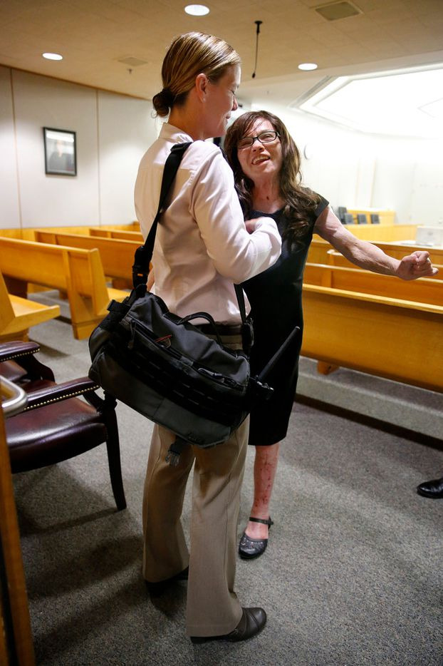 Burn victim Danyeil Townzen (right) received a hug from Dallas detective Gloria Doll after Townzen showed how much progress she's made by getting out of her wheelchair and walking a short distance in the 283rd District Court. Townzen took the stand and testified about being set on fire by her former boyfriend Matthew Gerth who plead guilty for the 2018 crime. He plead guilty to aggravated assault with a deadly weapon and serious bodily injury at the Frank Crowley courthouse in downtown Dallas, Friday, September 13, 2019.