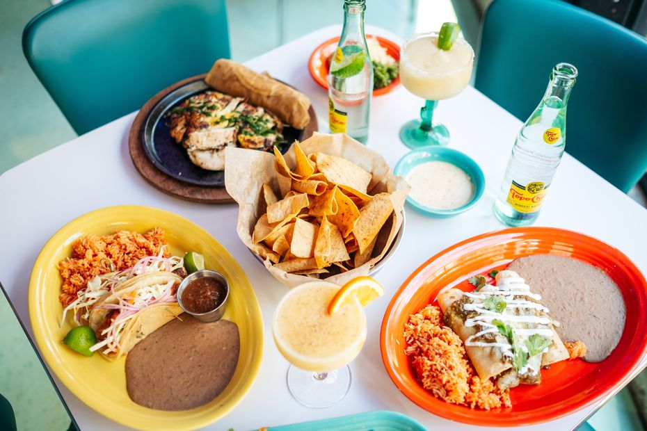 Some of the 'classicos' dishes at Queso Beso in downtown Dallas include grilled fish tacos (yellow plate) and chicken enchilada verdes (orange plate). The restaurant opens Dec. 13, 2019.
