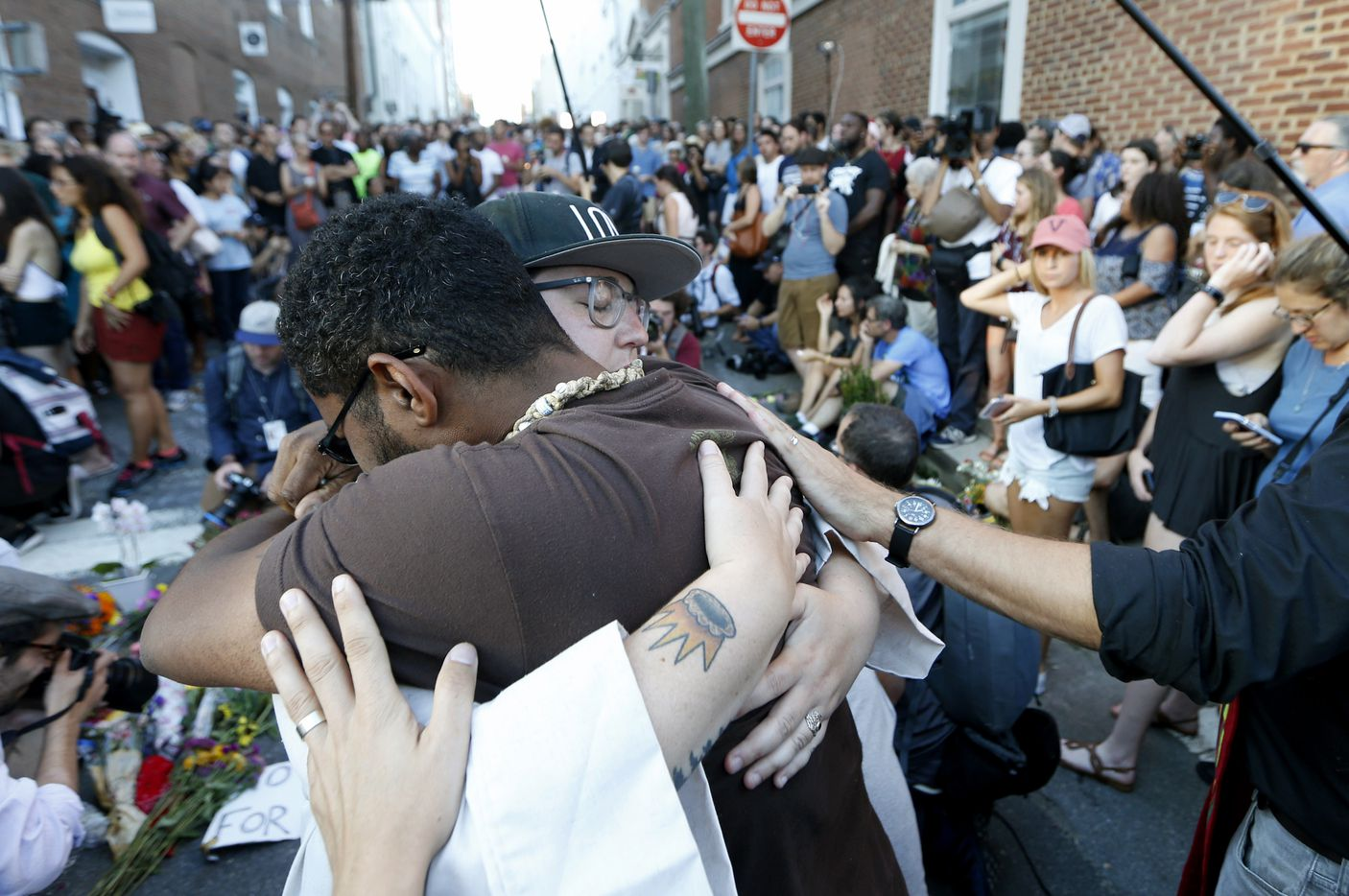 Brittney Cain-Conley (in a hat), lead organizer for Congregate Charlottesville, gets a hug from a supporter after she addressed the crowd during a vigil on Sunday at the site where Heather Heyer was killed a day earlier in Charlottesville, Va.