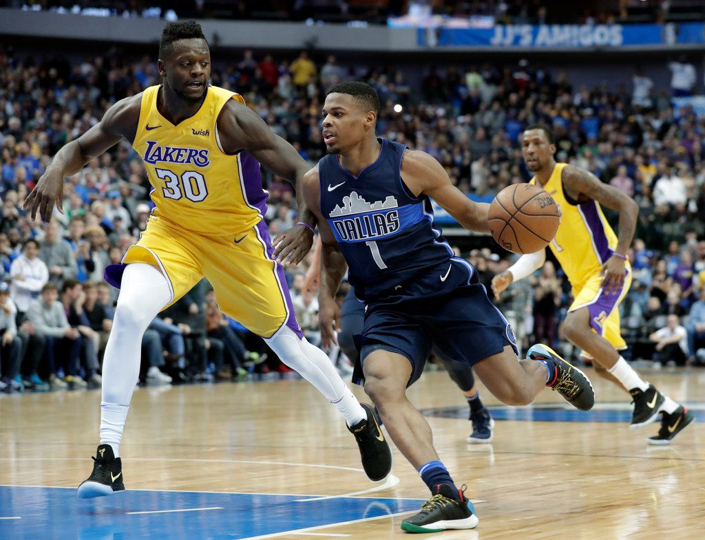 Los Angeles Lakers forward Julius Randle (30) defends as Dallas Mavericks guard Dennis Smith Jr. (1) moves to the basket in the second half of an NBA basketball game, Saturday, Jan. 13, 2018, in Dallas. The Lakers won in overtime, 107-101. (AP Photo/Tony Gutierrez)
