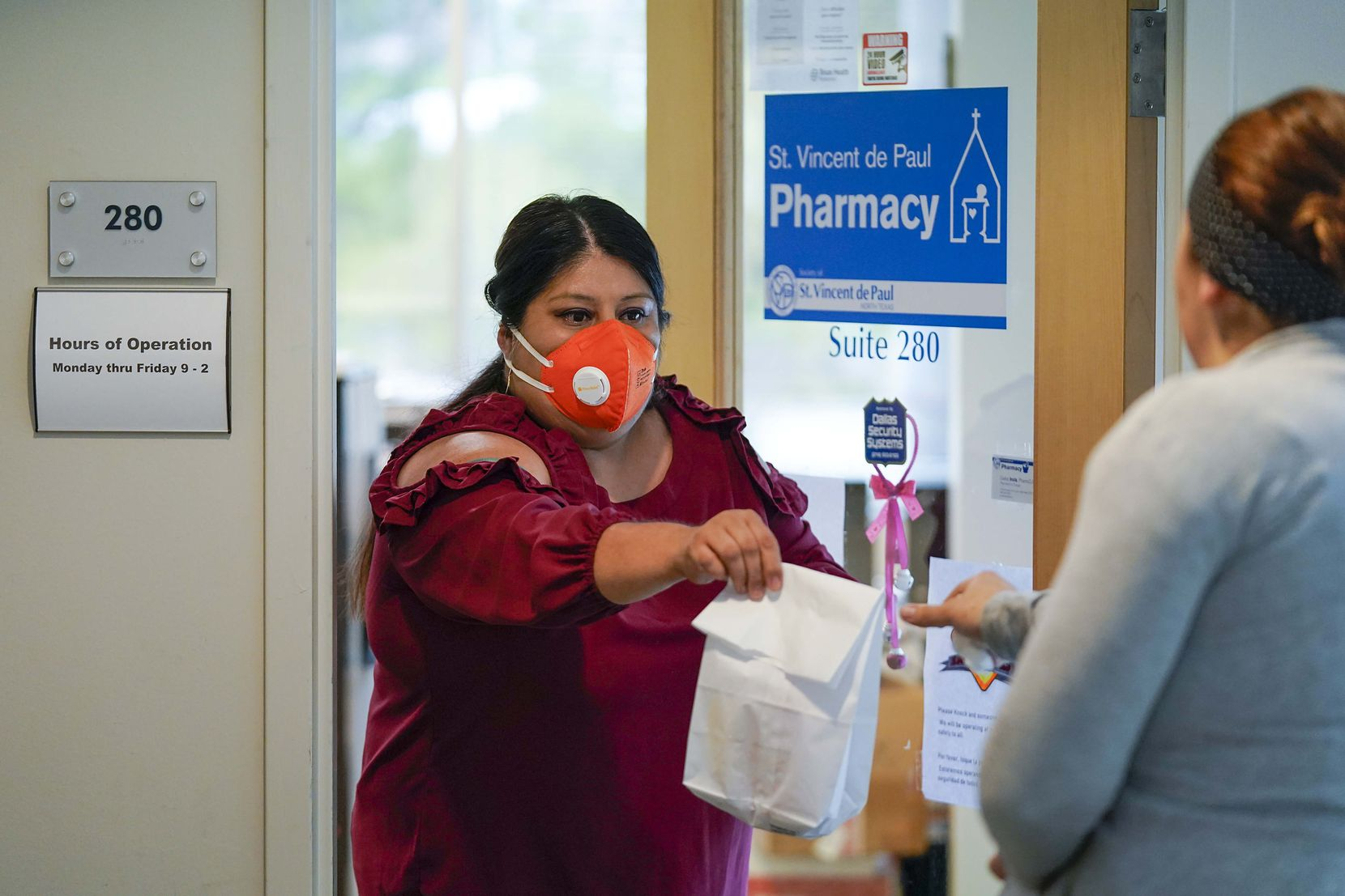 Intake Specialist Rosy Chavez handed a prescription to a client from the doorway at St. Vincent de Paul Pharmacy at the Northwest Community Center on Friday, April 3, 2020, in Dallas. The pharmacy has doubled its prescription volume as the coronavirus spreads in Dallas County.