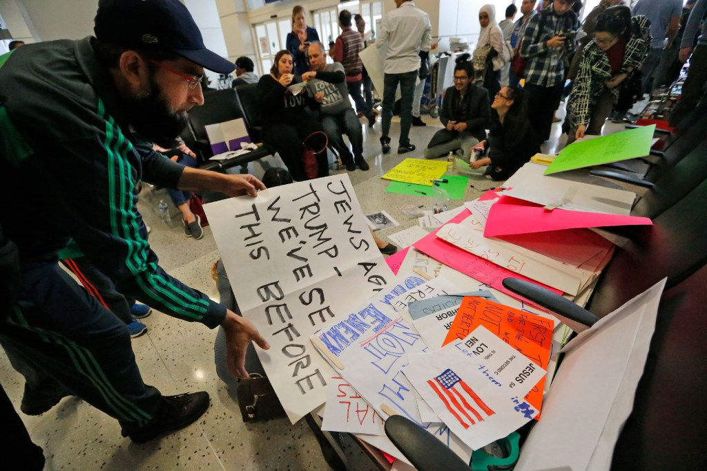 Protesters make signs to distribute in the waiting area at the international arrivals gate in Terminal D at DFW Airport on Sunday, January 29, 2017. (Louis DeLuca/The Dallas Morning News)