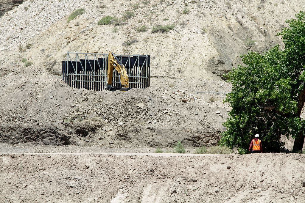 In a May 24, 2019 photo, a construction worker watches a section of fencing be moved for a privately-funded border fence on private land in Sunland Park, N.M. A leader with the group that's been raising funds to build a southern border wall on its own says they erected less than a mile of wall on private land in New Mexico over Memorial Day weekend.