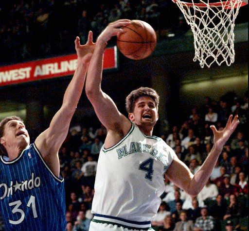 ORG XMIT: DNA101 Dallas Mavericks' Cherokee Parks (4) pulls down a rebound in front of Orlando Magic guard Anthony Bowie (14) during the fourth quarter in Dallas Monday night, Jan. 15, 1996. (AP Photo/Eric Gay)