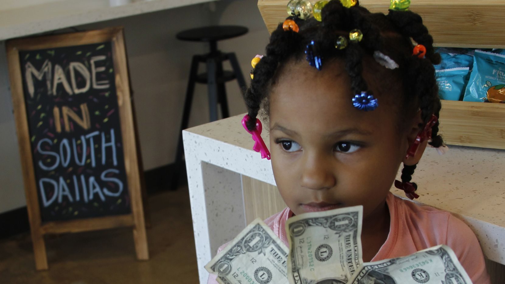 Miah Cooper, 5, ponders a variety of snacks available at the Southpoint Community Market. The new grocery store, opened by Cornerstone Baptist Church, had its grand opening on Juneteenth. The store is at 1645 South Boulevard in Dallas.