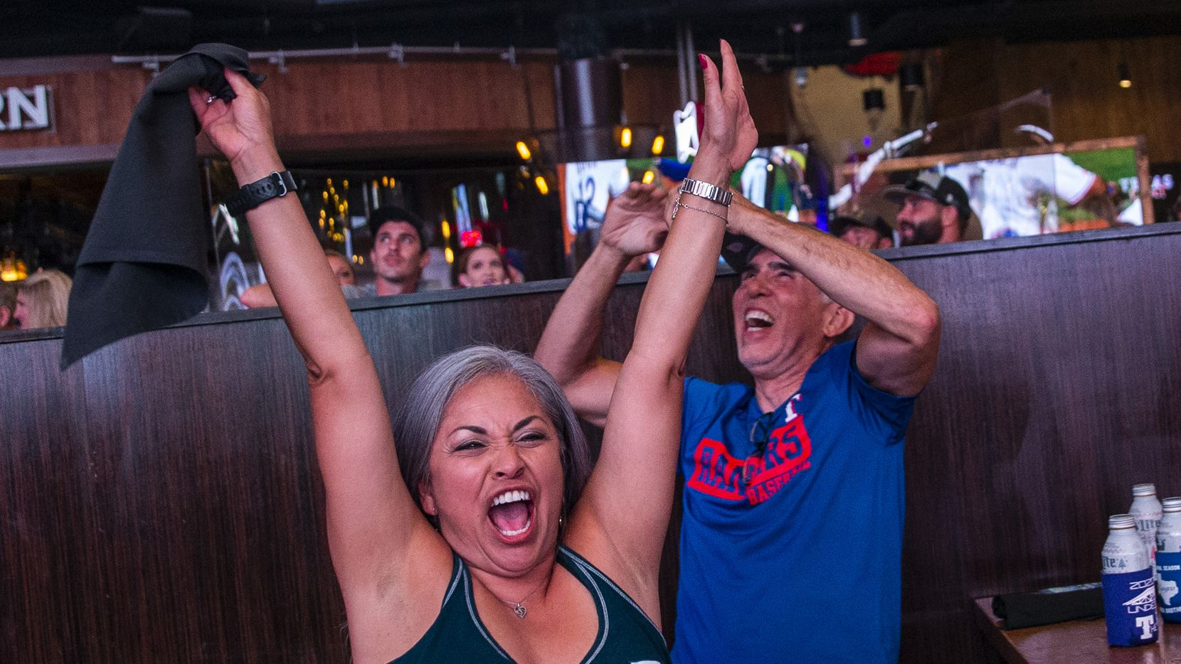 Claudia Borunda (left), from California, cheers with fans as the Texas Rangers win their opening day game of their season at Texas Live! in Arlington, Texas, on Friday, July 24, 2020. The Rangers played the Colorado Rockies at the new Globe Life Field stadium, but fans had to watch on televised screens outside due to the ongoing pandemic.