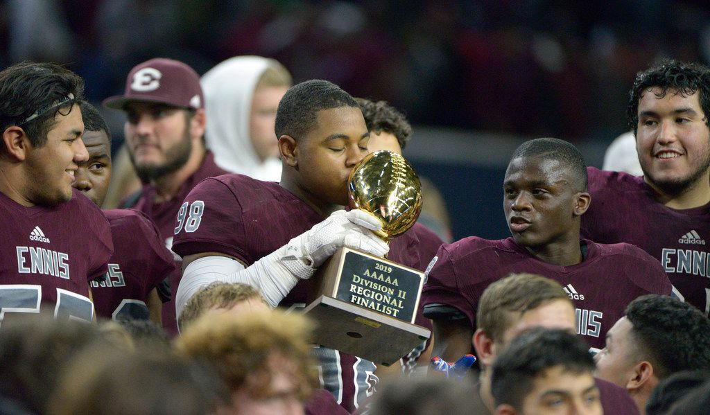 Ennis' Lazurus Becks (98) kisses the trophy after a Class 5A Division II Region  II semifinal high school football game between Frisco and Ennis, Friday, Nov. 29, 2019, in Frisco, Texas. Ennis won 17-0.