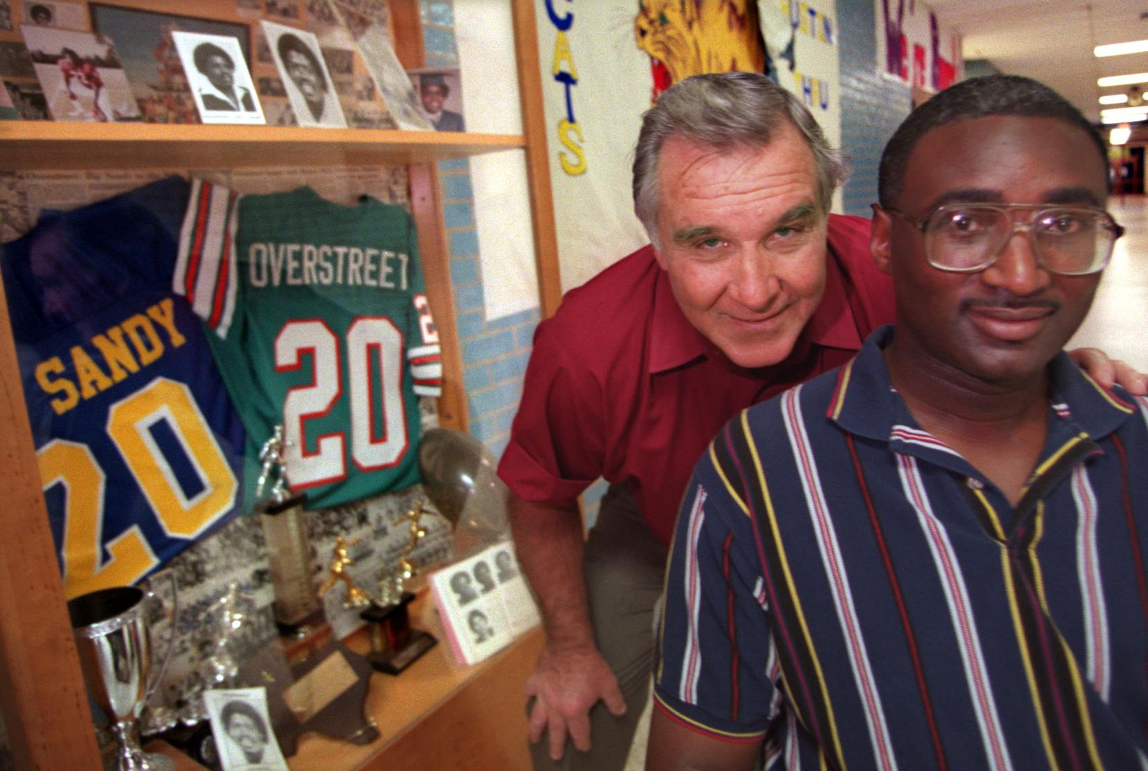 ORG XMIT: S1254B65D Former Big Sandy football coach Jim Norman (left) and former player Gary Chalk pose in front of the trophy case containing former player David Overstreet's memorabilia at the high school in East Texas Thursday afternoon.