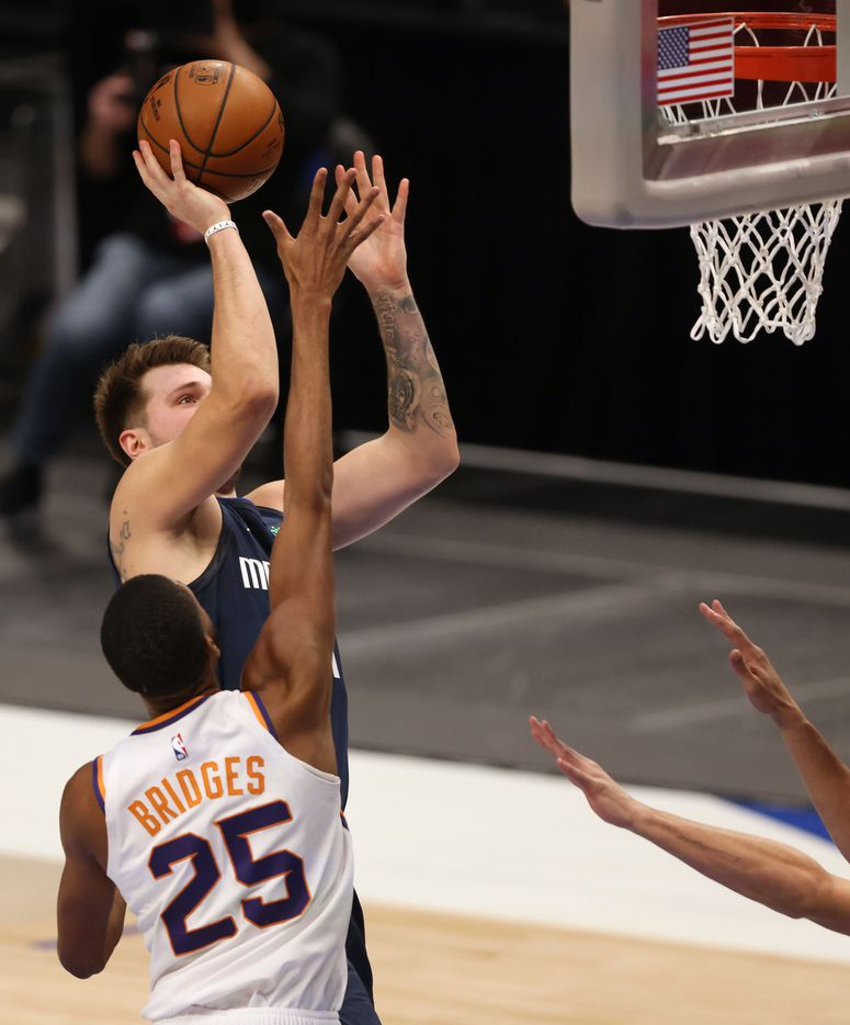 Dallas Mavericks guard Luka Doncic (77) pulls up for a shot in front of Phoenix Suns forward Mikal Bridges (25) during the second quarter of play at American Airlines Center on Monday, February 1, 2021in Dallas. (Vernon Bryant/The Dallas Morning News)