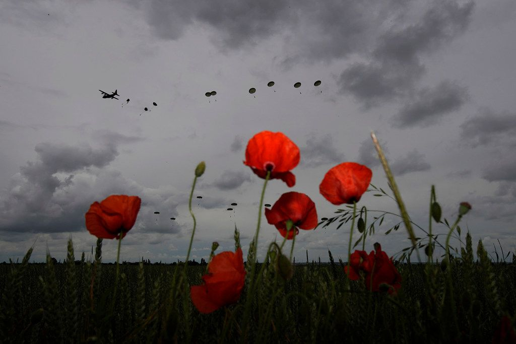 SANNERVILLE, FRANCE - JUNE 05: Poppies blossom in the grass as 280 paratroopers take part in a parachute drop onto fields at Sannerville on June 05, 2019 at Sannerville, France. Veterans, families, visitors and military personnel are gathering in Normandy on June 6th to commemorate the 75th anniversary of the Normandy Landings which heralded the Allied advance towards Germany and victory in Europe 11 months later.