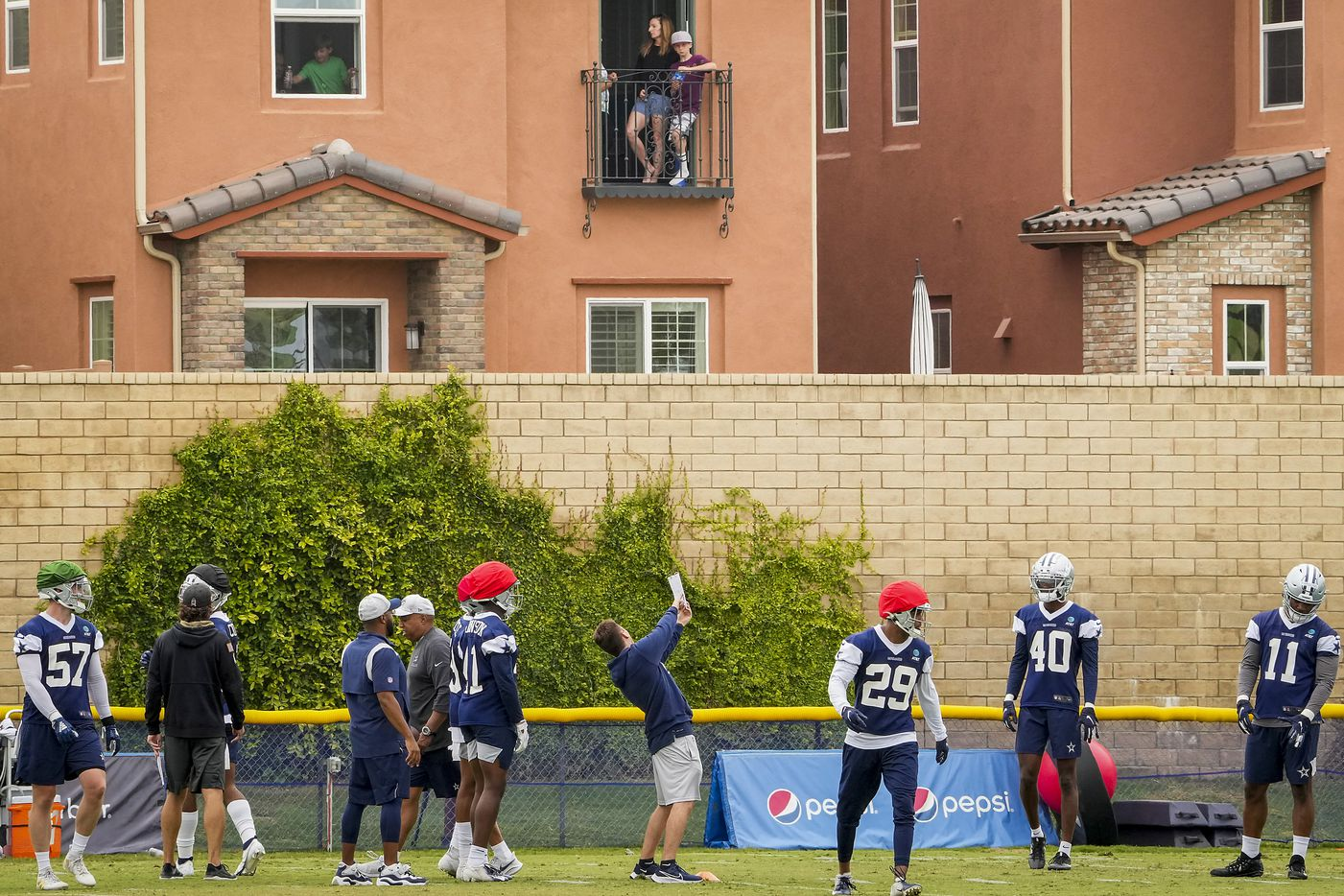 People watch from the balcony of a home adjacent to the complex during a Dallas Cowboys practice at training camp on Saturday, July 24, 2021, in Oxnard, Calif.