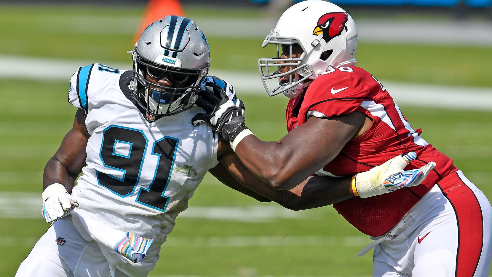 Kelvin Beachum #68 of the Arizona Cardinals blocks Stephen Weatherly #91 of the Carolina Panthers during the first quarter of their game at Bank of America Stadium on October 04, 2020 in Charlotte, North Carolina.
