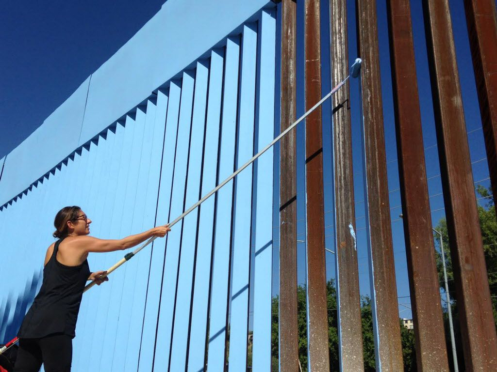 La artista Ana Teresa Fernández pinta un segmento de la barda en el lado mexicano de la frontera con Estados Unidos, en Nogales, México.(AP)