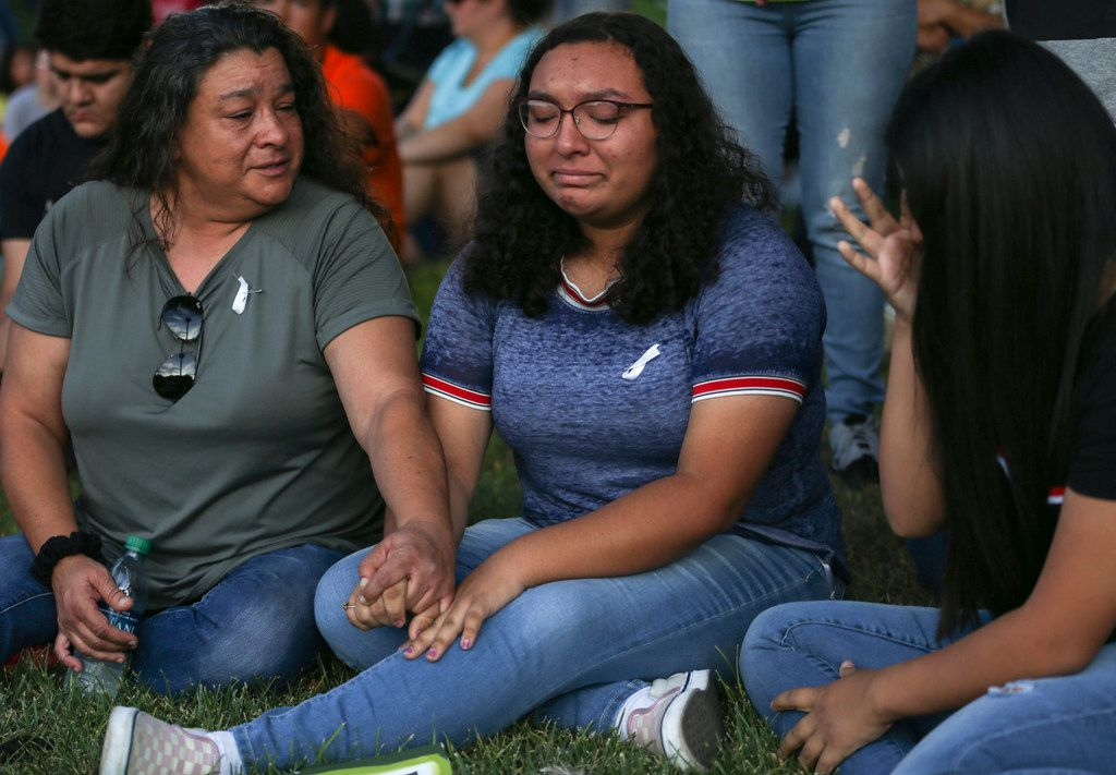 Christina Lopez (from left) comforts her daughter, Celia Lopez, 15, and Sajeili Carrasco, 15, who were both friends with Leilah Hernandez, a 15-year-old Odessa High sophomore killed in the attack, as community members gather for a prayer vigil at the University of Texas Permian Basin on Sunday, Sept. 1, 2019. At least seven people died after more than 20 people were shot Saturday when a gunman hijacked a postal truck and began shooting randomly in the Odessa area of West Texas, authorities say.(Ryan Michalesko/The Dallas Morning News)