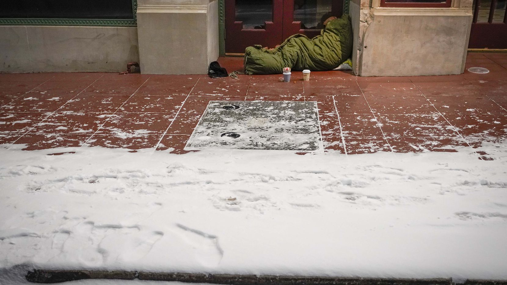With temperatures already falling into the single digits, a homeless person sleeps in the doorway of the Majestic Theater as a winter storm brings snow and freezing temperatures to North Texas on Sunday, Feb. 14, 2021, in Dallas.