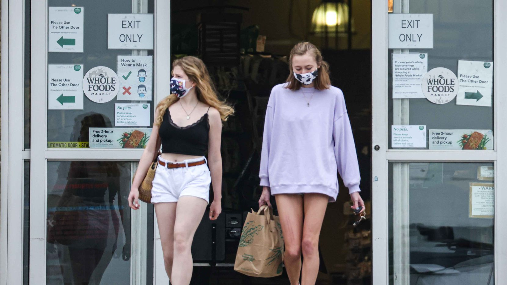 Emma Lloyd, 18, and Harper Jones, 18, leave Whole Foods Market on Abrams Rd as they wear masks even after COVID-19 mandates were lifted in March by Texas officials. Competitor Trader Joe's said Friday it will no longer require masks.