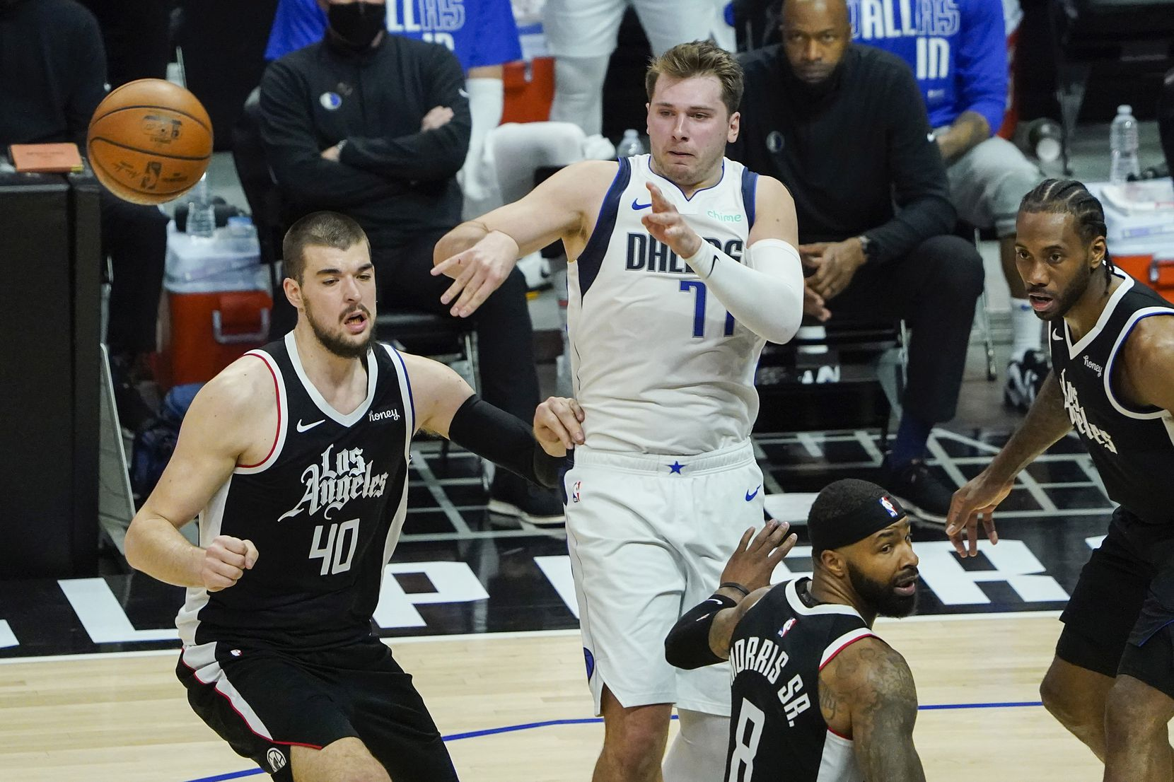 Dallas Mavericks guard Luka Doncic (77) passes the ball under pressure from LA Clippers center Ivica Zubac (40), forward Marcus Morris Sr. (8) and forward Kawhi Leonard (2) during the second quarter of an NBA playoff basketball game at the Staples Center on Wednesday, June 2, 2021, in Los Angeles.  (Smiley N. Pool/The Dallas Morning News)