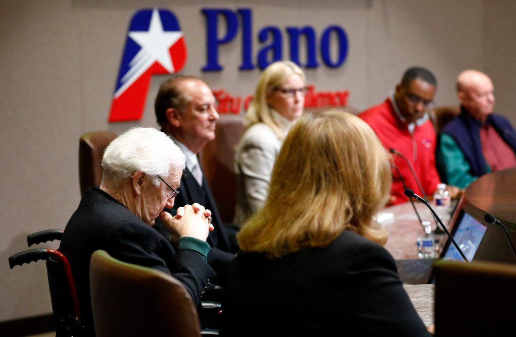 Plano city council member Tom Harrison (left) listens as fellow council call for his resignation following executive session in a specially called public meeting on Sunday.