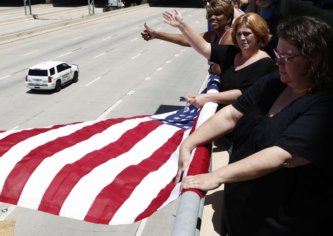 From left, Sandra Forte, Shelly Hughes, Pam Holt and other employees from SBB Management Company wave and give thumbs up to passing police vehicles as they proceed east on Interstate 635 to Restland Funeral Home, where Dallas police sergeant Michael Smith will be buried, on Thursday, July 14, 2016 close to TI Blvd in Dallas, Texas. Smith was one of five officers who were killed on Thursday, July 7, 2016, when a gunman targeted police during a Black Lives Matter rally in downtown Dallas.