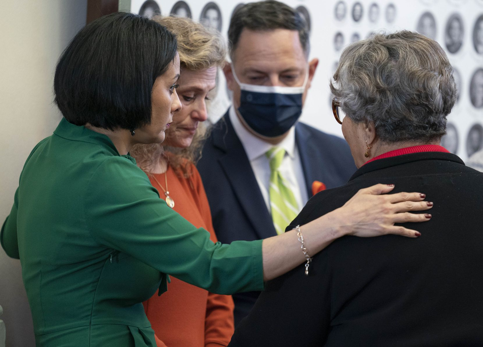 """Democratic colleagues surround state Rep. Donna Howard (in orange) after she challenged Republican sponsors of SB 8, the fetal """"heartbeat bill,"""" Wednesday in the Texas House. The bill passed second reading, 81-63, and is scheduled for a final vote that would send it to Gov. Greg Abbott's desk."""