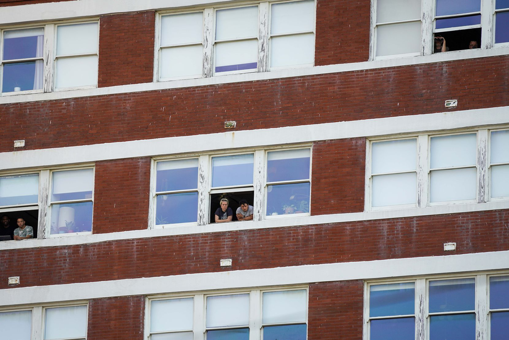 People watch from the windows of South Side on Lamar during protest against police brutality at the Dallas Police Headquarters on Friday, May 29, 2020, in Dallas.