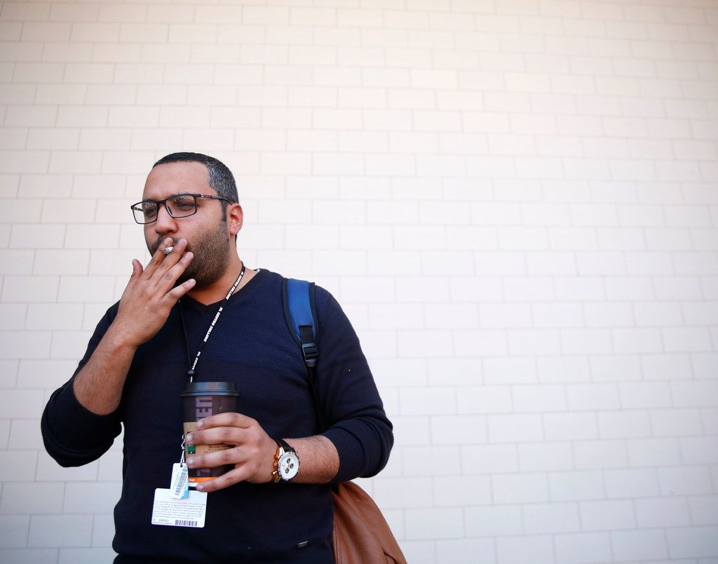 """Mohamed Khattab, 27, smokes a cigarette outside El Centro College in downtown Dallas. Khattab, who started smoking when he was 20-years-old, thinks it's appropriate that lawmakers are thinking of raising the legal age to 21, """"because I'm trying to quit now,"""" he said."""