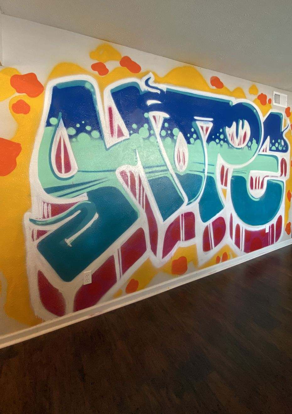 """A mural inside the Dallas Hope Center's current property reads """"Hope"""" in large, colorful letters."""