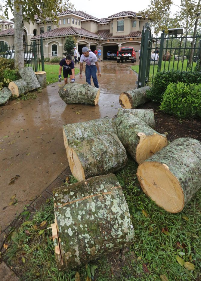 Crews cleaned up tree debris after a tornado spawned by Hurricane Harvey hit the Sienna Plantation subdivision southeast of Houston on Saturday.