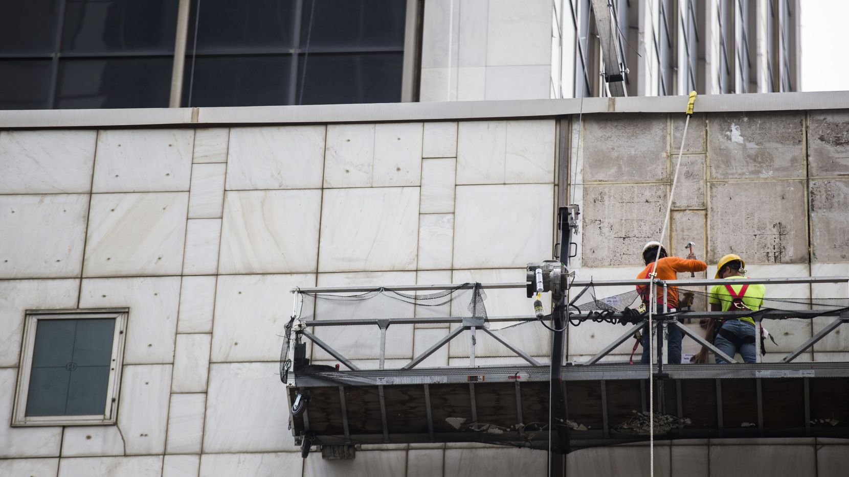Workers remove panels of marble off of the former First National Bank Tower in downtown Dallas. All of the marble on the skyscraper will be refurbished and replaced.