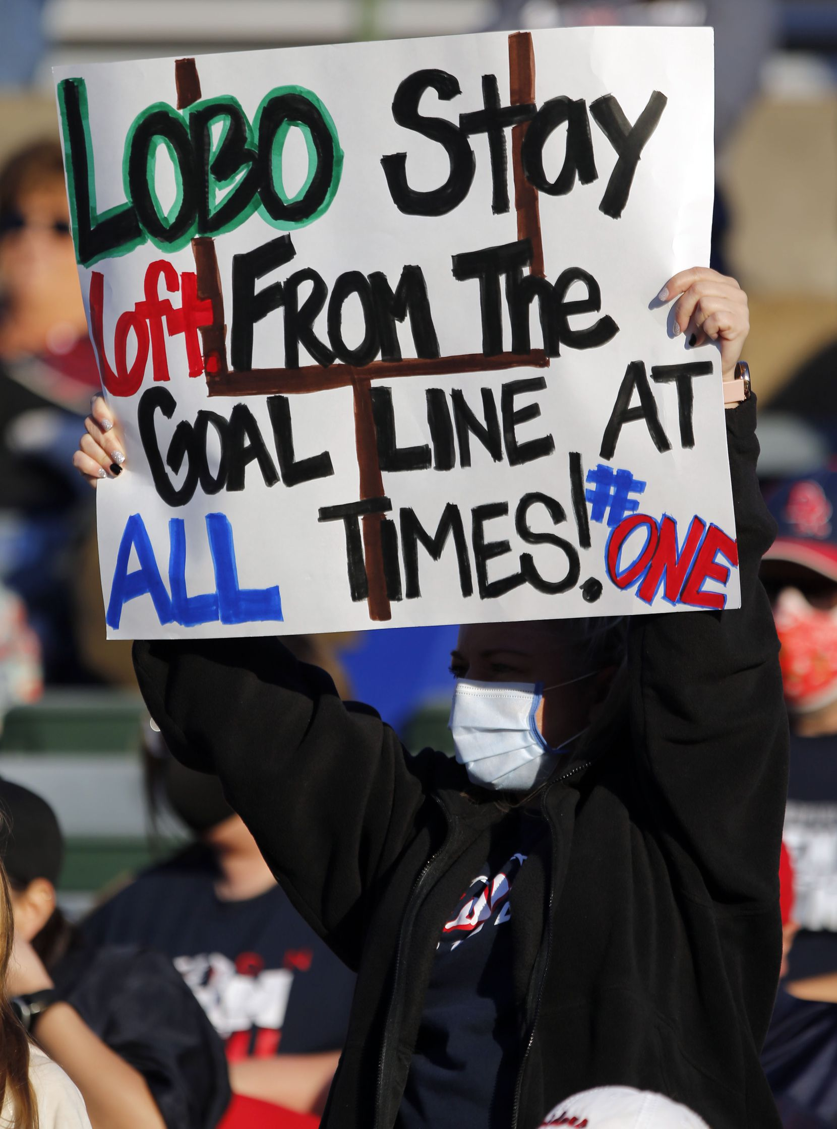 """A Denton Ryan fan holds a social distancing sign that reads, """"Lobo Stay 6ft from the Goal Line at all times!"""" during the second half of a Class 5A Division I Region I semifinal football playoff game that Ryan won 27-9 against Longview High at Mesquite Memorial Stadium in Mesquite on Saturday, December 26, 2020. (John F. Rhodes / Special Contributor)"""