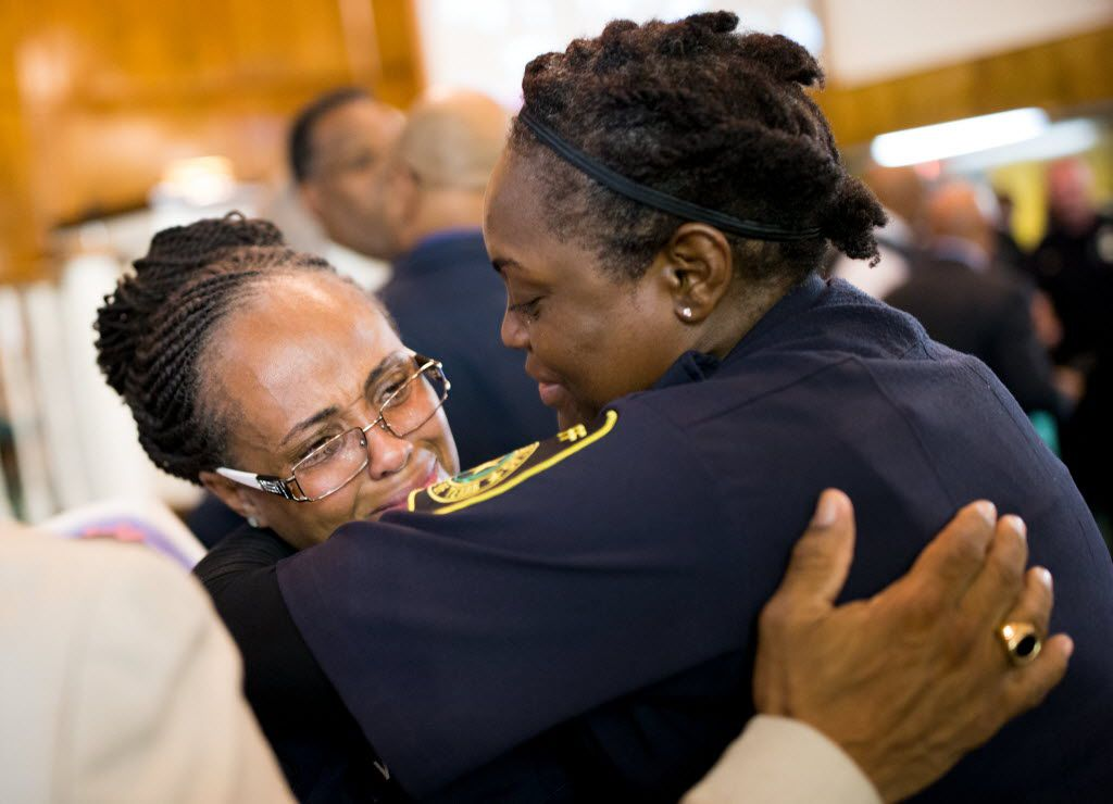Dallas County sheriff's Deputy Sgt. S. Wesley was comforted by fellow deputy C. Coleman during a prayer vigil hosted by Dallas Area Interfaith at Southern Hills Church of Christ on Sunday in Dallas.