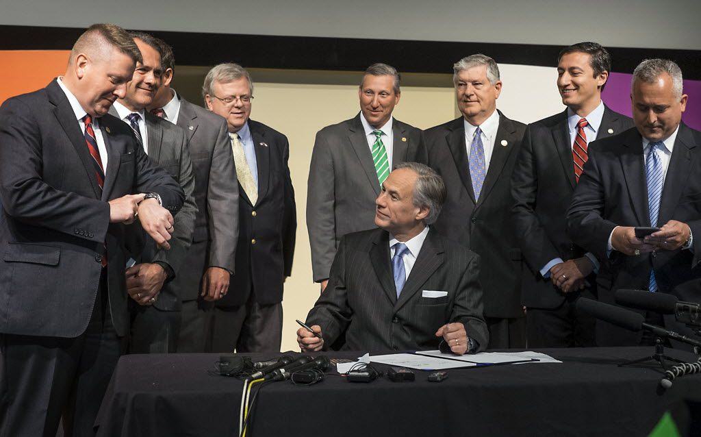 Gov. Greg Abbott, shown signing a 2015 bill that cut franchise-tax rates by 25 percent, could get another chance to sign legislation establishing certain triggers for future reductions. (2015 File Photo/Austin American-Statesman)