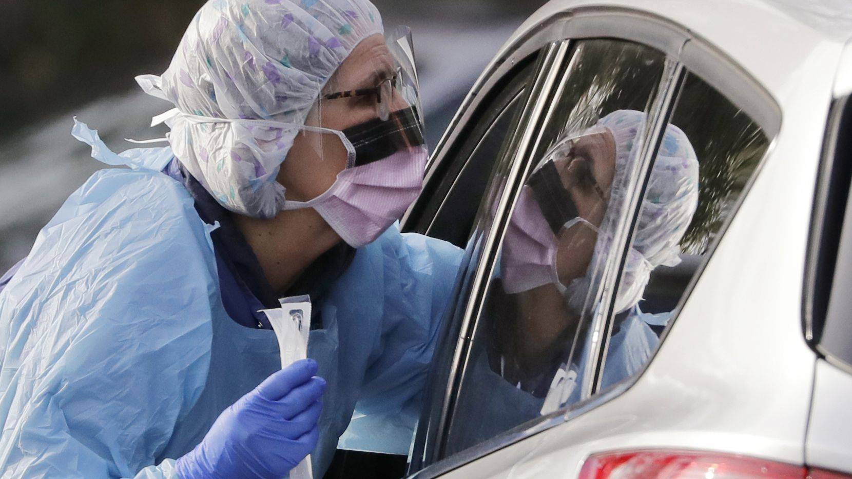 Laurie Kuypers, a registered nurse, reaches into a car to take a nasopharyngeal swab from a patient at a drive-through COVID-19 coronavirus testing station for University of Washington Medicine patients in Seattle, on March 17, 2020.