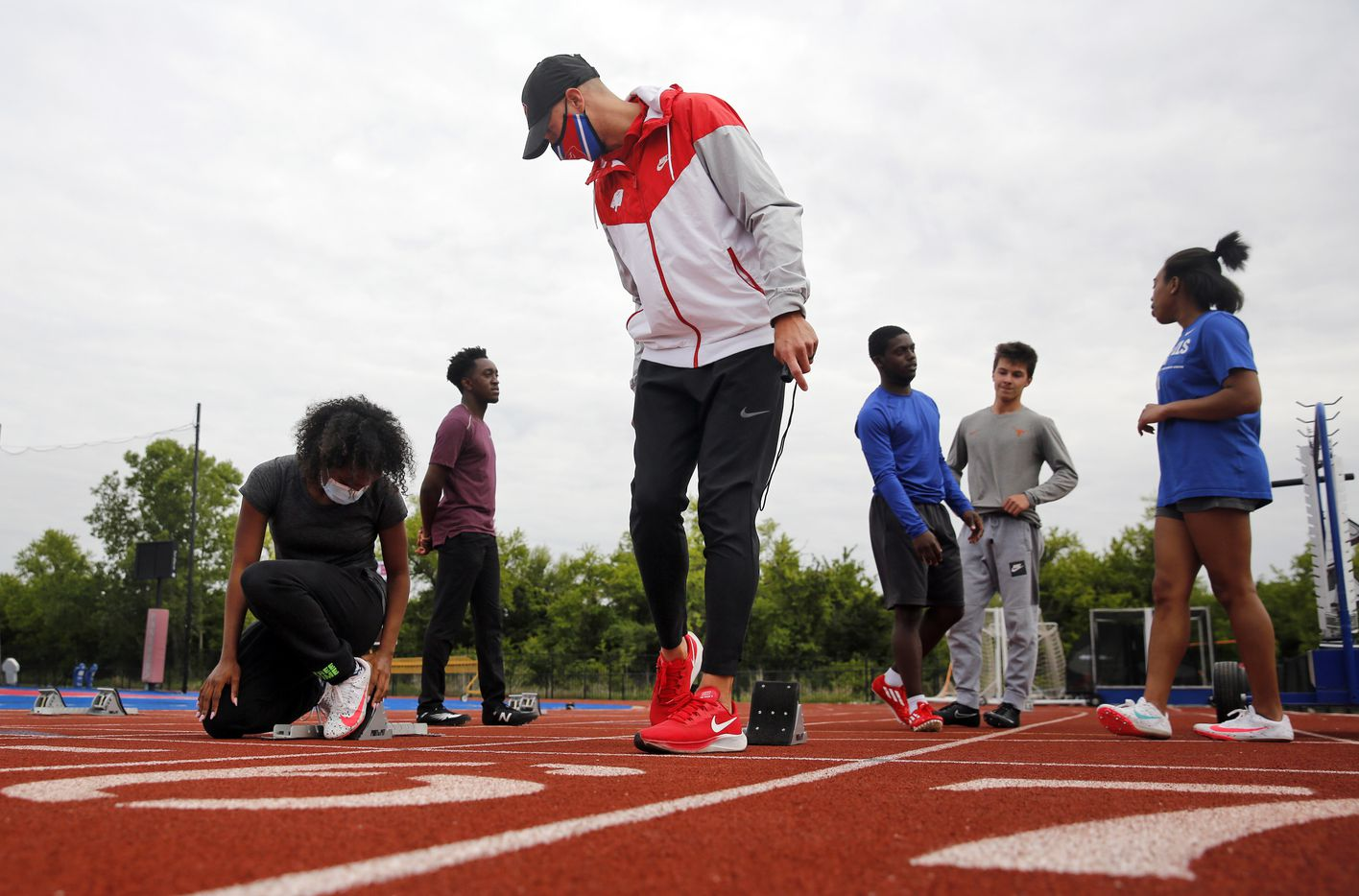 Parish Episcopal head track coach Jeremy Wariner shows start block technique to sophomore sprinter Samantha Ward (left) during practice at the Dallas school, Wednesday, April 21, 2021.  The former Arlington Lamar and Baylor star who won three Olympic gold medals -- one in the 400 meters and two in the 4x400 relay, took over the program after retiring from competition. (Tom Fox/The Dallas Morning News)