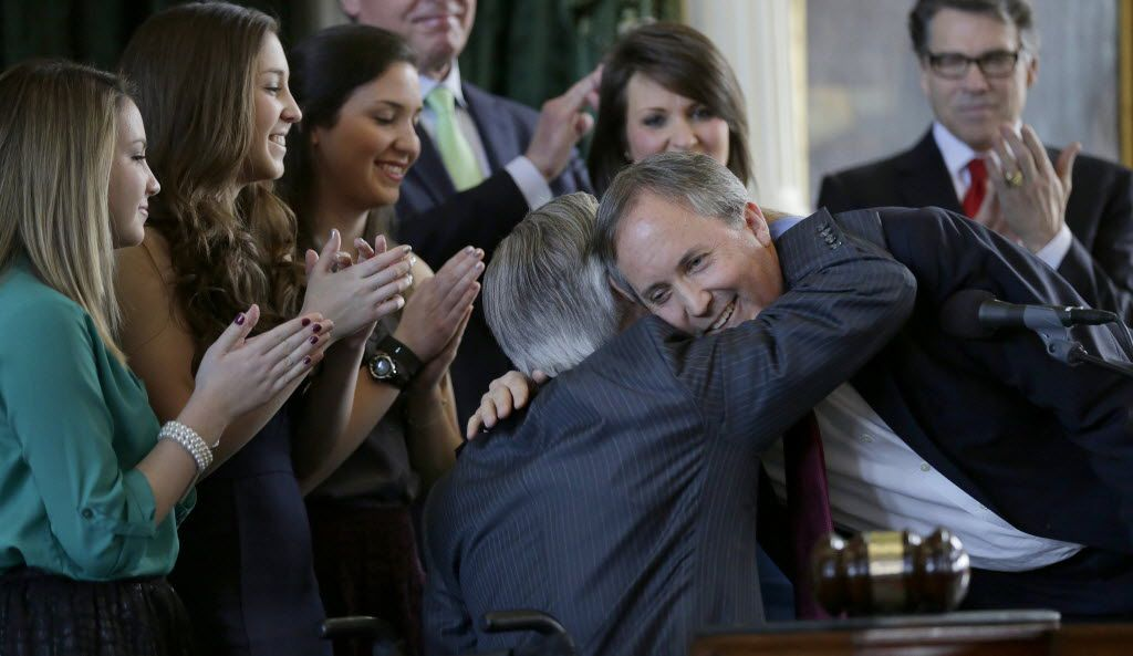 Ken Paxton (right) embraces Gov.-elect Greg Abbott after Paxton was sworn in as the Texas attorney general on Jan. 5, 2015, in Austin.